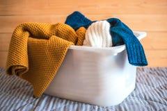 Behållare med tvätterit på soffan mot träbakgrund arkivfoton