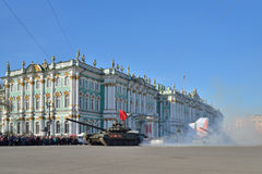 Behållare T-90 med en röd flagga i en puff av rök på slottsquaen Arkivbilder