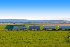 Behållaredrev över grönt fält fotografering för bildbyråer