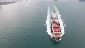 Behållarelastfartygsegling i det lugna havvattnet på en molnig dag i dimman i skott för antenn 4k lager videofilmer