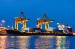 Behållarelastfrakter sänder med den arbetande kranbron i shipya Arkivbilder