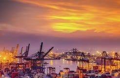 Behållarelastfrakter sänder med den arbetande kranbron i shipya Royaltyfri Foto