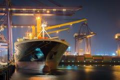Behållarelastfrakter sänder med den arbetande kranbron i skeppsvarv på skymning för logistisk importexport royaltyfri bild