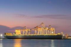 Behållarelastfrakter sänder med den arbetande kranbron i skeppsvarv på skymning för logistisk importexport royaltyfria foton
