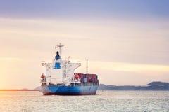 Behållarelastfrakter sänder med den arbetande kranbron i skeppsvarv på skymning för logistisk importexport royaltyfri fotografi