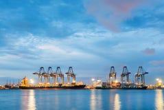 Behållarelastfrakter sänder med den arbetande kranbron i skeppsvarv på skymning för logistisk importexport arkivfoton