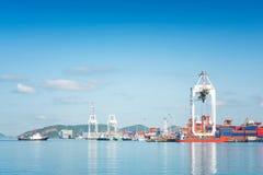 Behållarelastfrakter sänder med den arbetande kranbron i skeppsvarv på skymning för logistisk importexport arkivbilder