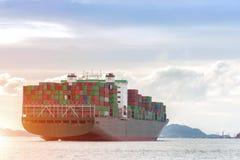 Behållarelastfrakter sänder med den arbetande kranbron i skeppsvarv på skymning för logistisk soluppgång för importexportbakgrund arkivbild