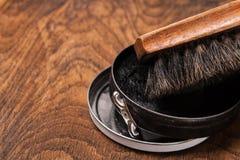 Behållaren av skokräm och borstar på trä Royaltyfria Bilder