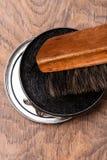 Behållaren av skokräm och borstar på trä Royaltyfri Fotografi