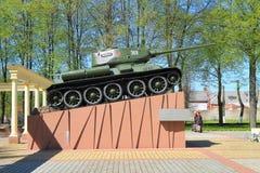 Behållaren T-34 på en hög sockel, ett minnes- komplex på en massgrav av de sovjetiska soldaterna royaltyfria foton