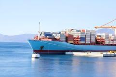 Behållareskepp med behållare som ska stöttas i portskeppport på horisont/lasttrans. vid havet och gods som lastar av process royaltyfri foto
