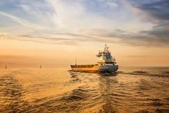 Behållareskepp på havsvägen under solnedgång. Arkivbilder