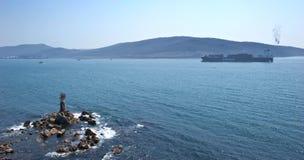 Behållareskeppet Fesco Diomid passerar en liten fyr Nakhodka fjärd Östligt (Japan) hav 26 04 2015 Royaltyfri Bild