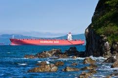 Behållareskeppet Monte Sarmiento passerar den steniga udden Nakhodka fjärd Östligt (Japan) hav 27 05 2014 Arkivfoto