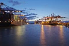 Behållareskyttel på terminalen i hamn i aftonen Arkivfoto