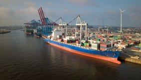 Beh?llareterminal med skepp i porten av Hamburg p? soluppg?ng royaltyfri bild