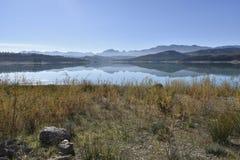 Behållarvatten med reflexionen av bergen i vattnet arkivfoto