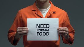 Behöv det normala matuttrycket på papp i händer av den Caucasian fången, protest stock video