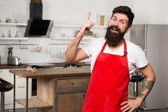 Behöv kulinarisk inspiration Hur man vänder att laga mat hemma in i vana Ställning för förkläde för skäggig hipster för man röd i arkivbild