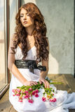 Behaartes Mädchen in einem Hochzeitskleid und Make-up mit einem festlichen mit einem Blumenstrauß von Rosen Stockfotografie