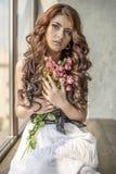 Behaartes Mädchen in einem Hochzeitskleid und Make-up mit einem festlichen mit einem Blumenstrauß von Rosen Lizenzfreies Stockfoto