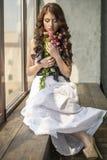 Behaartes Mädchen in einem Hochzeitskleid und Make-up mit einem festlichen mit einem Blumenstrauß von Rosen Lizenzfreie Stockfotografie
