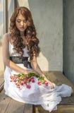 Behaartes Mädchen in einem Hochzeitskleid und Make-up mit einem festlichen mit einem Blumenstrauß von Rosen Stockfotos