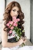 Behaartes Mädchen in einem Hochzeitskleid und Make-up mit einem festlichen mit einem Blumenstrauß von Rosen Lizenzfreie Stockbilder