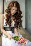 Behaartes Mädchen in einem Hochzeitskleid und Make-up mit einem festlichen mit einem Blumenstrauß von Rosen Lizenzfreies Stockbild