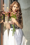 Behaartes Mädchen in einem Hochzeitskleid und Make-up mit einem festlichen mit einem Blumenstrauß von Rosen Lizenzfreie Stockfotos