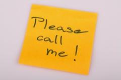 Behaga kallar mig anmärkningen på orange klistermärkeanmärkning på vit Royaltyfri Foto