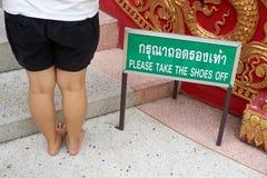 Behaga tar skorna av etikett med kvinnabenet Arkivbild