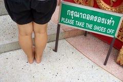 Behaga tar skorna av etikett med kvinnabenet Royaltyfria Foton