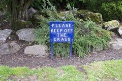 Behaga uppehället av gräsblått undertecknar in den privata trädgården royaltyfria bilder