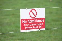Behaga uppehället av sportgräsgraden under reparationstecken fotografering för bildbyråer