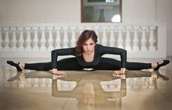 Behagfull ballerina som gör splittringarna på marmorgolvet Ursnygg balettdansör som utför en splittring på glansigt golv royaltyfria bilder