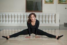 Behagfull ballerina som gör splittringarna på marmorgolvet Ursnygg balettdansör som utför en splittring på glansigt golv arkivfoto