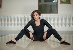Behagfull ballerina som gör splittringarna på marmorgolvet Ursnygg balettdansör som utför en splittring på glansigt golv fotografering för bildbyråer