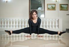 Behagfull ballerina som gör splittringarna på marmorgolvet Ursnygg balettdansör som utför en splittring på glansigt golv Arkivbild