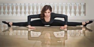 Behagfull ballerina som gör splittringarna på marmorgolvet Ursnygg balettdansör som utför en splittring på glansigt golv Arkivbilder
