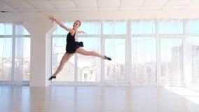 Behagfull ballerinadansare som utför ett hopp i den vita studion stock video