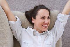 Behagfull flicka som tycker om fri tid som ligger på soffan Arkivbilder