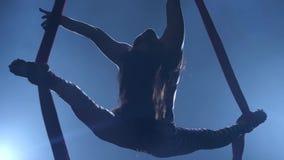 Behagfull gymnast som utför flyg- övning med rött silke på blå ljus bakgrund l?ngsam r?relse closeup 336 stock video