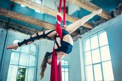 Behagfull gymnast som utför flyg- övning på vinden royaltyfri foto