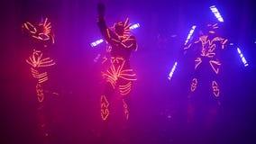 Behagfulla flickor och grabbar som dansar i de glödande dräkterna Laser-show, ljus show, LEDD show lager videofilmer