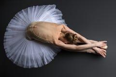 Behagfullt ballerinasammanträde på golvet royaltyfri foto