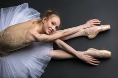 Behagfullt ballerinasammanträde på golvet arkivbild