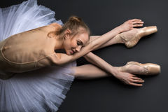 Behagfullt ballerinasammanträde på golvet royaltyfria bilder