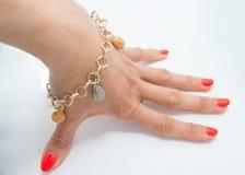 Behagfullt guld- armband på kvinnahanden royaltyfri foto